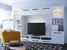 En stue med en stor multimedieløsning, der består af et hvidt tv-bord, reoler med låger af frostet glas og låger og skuffefronter i hvid højglans