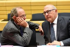 French Finance Minister Michel Sapin (R) speaks with Italian Finance Minister Pier Carlo Padoan during an emergency Eurogroup finance ministers meeting on Greece at the European Council in Brussels, on June 22, 2015. AFP PHOTO/Emmanuel DunandEMMANUEL DUNAND/AFP/Getty Images