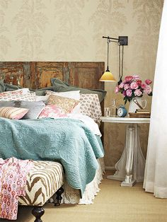 Add personality to the bedroom with a mix of patterns and a unique headboard like this old door