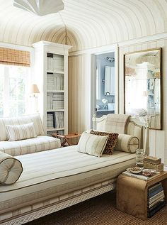 """The sumptuous study, awash in Carolina Irving's Patmos Stripe fabric, doubles as a guest bedroom. """"Having the daybed in the center allows for the feeling of a library and a spot for people to sleep,"""" says Mark."""