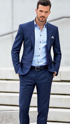 Navy blue suit and light blue dress shirt with white pocket square and black belt.