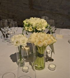Tulips, freesias, lisianthus  <3 the separate vases for centerpieces