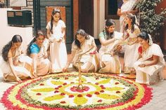 "Ladies busy preparing the ""Flower Rangoli"" on the occasion of Onam."