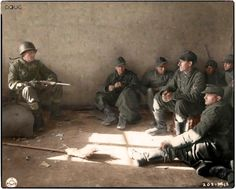 An Infantryman of the 301st Regiment, 94th Infantry Division, US Third Army, guards a group of German prisoners in a house in Schillingen, Germany. 15th of March 1945.