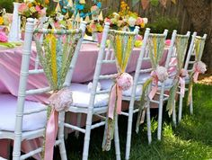 I love the riot of spring colors here. The torn strips of fabric on the back of the chairs tied with the peonies is so inventive.