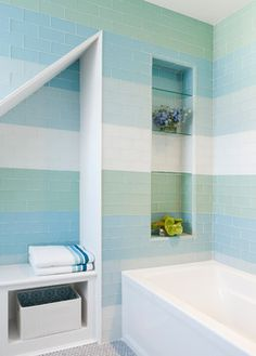 """This glass tile is really beautiful and looks like sea glass,"" Gomez says. ""You can see into this bathroom as you go up the stairs, and I thought, ""Let's just stripe the walls and have some fun with it."""