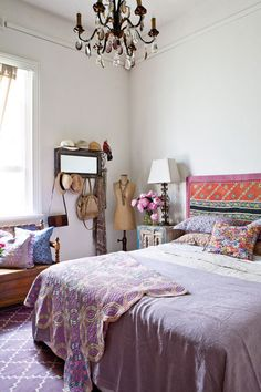 cozy bedroom, love the mirrored shelf with hooks for hats and bags and love the chandelier.