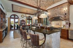 The Old World kitchen wows with a barrel ceiling and prominent brick range hood. Seating at the center island carries over to a small breakfast nook. Old World Kitchens, Cool Kitchens, Dream Kitchens, Coral Gables, Barrel Ceiling, Island With Seating, Mansions For Sale, Expensive Houses, Range Hoods