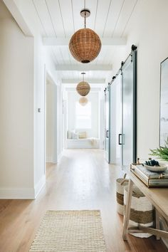 Dream Home: A Beach Inspired Beauty in ChicagoBECKI OWENS - modern coastal hallway with rattan chandelier and jute rug, modern coastal foyer table, Dream Home: - Modern Country, Modern Coastal, Coastal Farmhouse, Coastal Homes, Coastal Style, Coastal Decor, Farmhouse Ideas, Coastal Country, Coastal Entryway