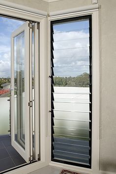louvre windows next to folding glass doors which open onto the deck