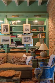 Because the living room lacked windows, custom bookshelves backed with mirrors were installed for added light. Thanks to a patterned rug, seafoam green paint, and pictures hung in slightly unconventional spots, the room's traditional features take on a more relaxed feel, as you would expect in the Big Easy.   - CountryLiving.com