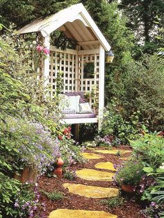 """Stepping Stone Path Leading to a Cozy Arbor """"Stepping stones can be a great way to beckon guests to a hidden spot, such as this cozy white arbor. Here, the stones blend beautifully with the landscape, easily visible while still retaining an earthy appeal. Add to your outdoor decor by framing the path with blooming flowers and lush greenery."""""""