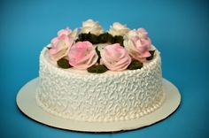 One tier traditional buttercream iced cake with light pink roses, chocolate leaves and delicate scrolling on the side