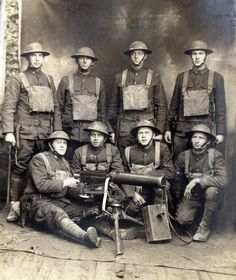 A group of American soldiers poses with an M1917 Browning machine gun holstered M1917 .45 revolvers Brodie helmets and gas masks ca. 1917. [757  899]