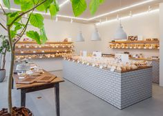 Fresh loaves and sugary treats are presented alongside wooden surfaces, ceramic tiles and plants at this renovated bakery in Kiryu, Japan.