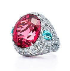Ring of an oval cut pink spinel with two pear shaped blue cuprian elbaite tourmalines and round diamonds.