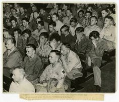 Faces of German POWs, captured by Americans, watching a film about a concentration camp.