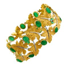 1970s Buccellati Emerald and Gold Bracelet. A naturalistic 18k yellow gold and emerald bracelet by Buccellati, the highly flexible band of foliate design composed of eighteen textured gold leaves, spaced by 18 cabochon emeralds weighing approximately 27.00 carats, gross weight 42.5 grams, length 7 1/2 inches, width 1 1/4 inches, signed Buccellati, Italy, numbered 32830. The width and size of this bracelet along with the richly colored emeralds make this bracelet a statement piece.