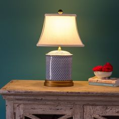 Contemporary Ceramic Table Lamp - A contemporary and pretty blue and white Chinese ceramic table lamp with lined lamp shade.    The shade is topped with a black ceramic ball fastening it in place.    This very striking table lamp is mounted on a bronze coloured base.