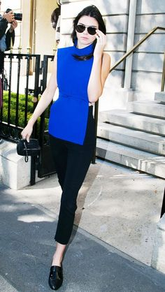 Kendall Jenner wears a blue belted top with cropped black pants and oxfords