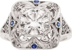 Art Deco Diamond, Platinum Ring  The ring features a round brilliant-cut diamond measuring 7.77 - 7.75 x 4.58 mm and weighing approximately 1.65 carats, accented by single-cut diamonds and round-shaped blue stones, set in platinum