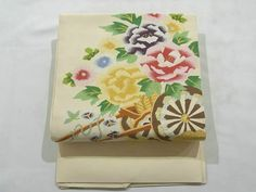 This is a Tsume tsuzure Nagoya obi with a design of flower cart, which is woven.  'Botan'(peony), 'kiku'(chrysanthemum) and some other flowers are designed on it