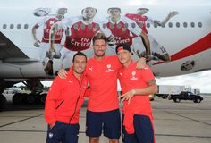 LONDON, ENGLAND - JULY 12:  Santi Cazorla, Olivier Giroud and Mesut Ozil of Arsenal in front of their images on the Emirates plane at Stansted Airport on July 12, 2015 in London, England.  (Photo by David Price/Arsenal FC via Getty Images) *** Local Caption *** Santi Cazorla; Olivier Giroud; Mesut Ozil