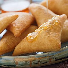 Tender warm pillows of fried dough, sprinkled with cinnamon sugar and drizzled with honey.