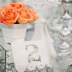 centerpieces: orange roses w/ white & silver vases.