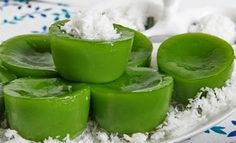 Kue Lumpang. Sweet and sticky steamed pandan cake coated with salty coconut grated.