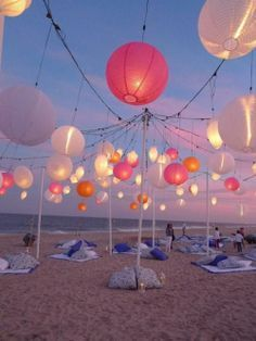 beach wedding idea- instead of chairs have everyone on blankets and pillows with the lanterns  above