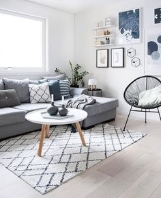 Stue, grå sofa med pyntepuder, tæppe, billeder, stol og hvidt sofabord