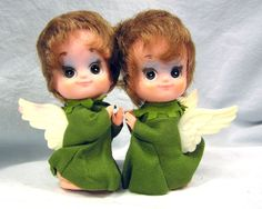 """At 5.5"""" tall, kneeling on their knees with hands raised in prayer and wings straight out for balance. Small latex bodies with enormous latex heads. Each sweet angel is topped with brown curls framing her lovely face with huge brown eyes shaded in light blue eye shadow, brown eyeliner and lashes, rosy cheeks and pink kindly grinning lips. 