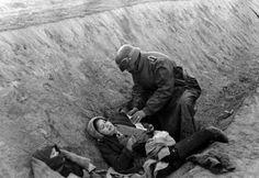 Un soldado alemán aplica un vendaje a una civil rusa herida que se refugiaba con su bebé [II Guerra Mundial, c. 1941].
