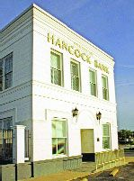 HANCOCK BANK BUILDINGBay St. Louis, MS  100 South Beach Boulevard  This Hancock County bank opened for business in 1899, boasting total assets of $18,277. The corporation now has 164 offices in four states, still maintaining this original branch. The stately masonry building has been completely restored and features a flat parapet roofline and raised corbels as wall supports. It is the oldest surviving two-story building in the city.