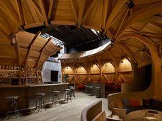 estrutura de madeira cria área semi fechada em bar americano