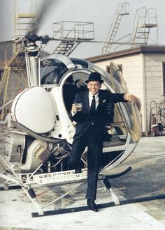 Frank Sinatra stepping out of a helicopter with a drink.