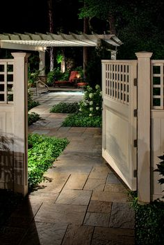A smooth cedar entry gate and fence opens above a dimensional full color range bluestone path. The cross-lapped lattice fence topper repeats the shadow pattern created as downlight casts through the pergola's rafters and purlins.