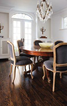 Sillas de comedor tapizadas en terciopelo de carbón vegetal rodean una antigua mesa redonda. Una araña de cristal y un par de apliques de pared ramificados añaden brillo y un toque de glamour