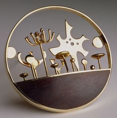 "Fisch's 'Gold Garden' pin (14K gold, rosewood, 1963). ""Fisch began as a ceramicist and switched to jewelry because, as she recounted in an oral history, ""I went looking in the community for a place to work, and what I found were jewelry studios…"" Uninspired by ""what you would see in jewelry stores,"" she fell in love instead with imposing Egyptian and pre-Columbian ceremonial pieces."""