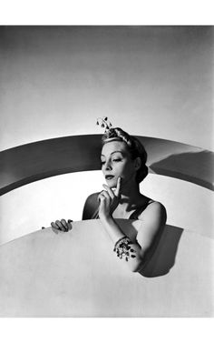 Helen Bennett wearing hair ornament of quivering gold bells, which also form her bracelet; both by Mainbocher. Vogue, March 1938