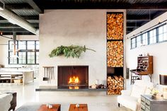 Fireplace with evergreen branch above and tall shelves for cut firewood