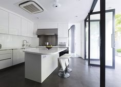 #Home & #Apartment White Sleek Kitchen Island With 2 White Gloss Bar Stool Big Glass Door White Gloss Cabinet Big Stainless Kitchen Drawer And Backsplash Grey Floor White Long Curtain Beauteous Luxury Mansion With an Endearing Monochromatic Interior by Aemer Architects