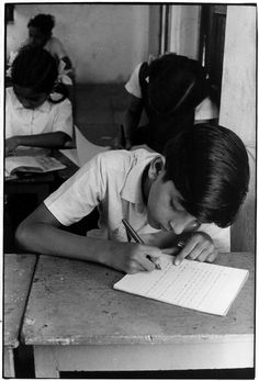 Boy sitting at desk writing at school.. From Duke Digital Collections. Collection: William Gedney Photographs and Writings. Mark: None. Date of print: Unknown.