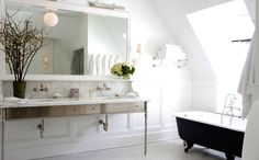 Classic meets contemporary bath.  Long wall mirror, satin nickel vanity, wall-mount faucets, picture lights, wainscoting, claw-foot tub, and flood of natural light | Sage Design
