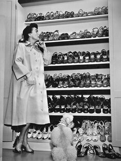 Joan Crawford gazing at a plethora of awesome mid-century shoes. Dog by her feet.
