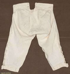 """LINEN KNEE BREECHES, AMERICAN, 1760-1770 White home spun raised pin-stripe linen, cut on cross grain, wide W band w/ 3 CF self-covered buttons & pair smaller side buttons to hold up wide fall, 2 pair sewn eyelets at CB W band, 4 buttons & tabs for knee buckles on each leg, gathered baggy seat, W 27+"""", Inseam 17.5"""", excellent. James Kochan - Don Troiani Collections"""