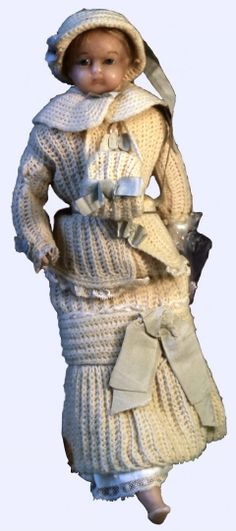 1870 Doll Culture: English Medium: wax Wax doll with rag body with blue glass eyes and fair hair. Wearing a white and blue crochet dress, half length jacket with separate cape collar, hat and muff edged with lace and trimmed with blue bows. Lace socks and brown heeled and bucked shoes.