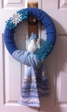 1 pool noodle duct taped into a circle 2 old scarves; one sewn around the noodle, the other wrapped around the bottom 1 snowman ornament  5 snowflakes  Voila! You have a Winter Scarf Wreath.