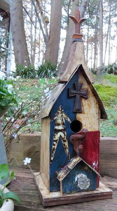 Patriotic theme birdhouse is hand crafted with eclectic and rustic style. Made from reclaimed materials, the Small Americana boasts aged red, white & blue theme, vintage iron adornments and crystal kn